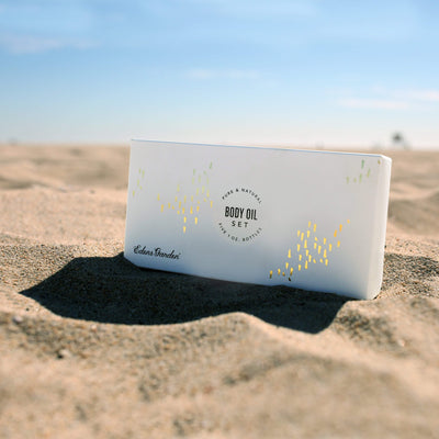 A beach with the packaging for the Set of 5 essential oil body oil to use instead of lotion by Edens Garden