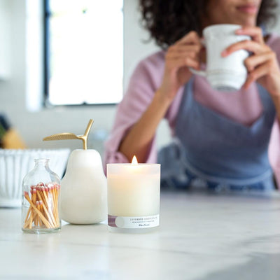 Woman drinking tea next to Lavender Magnolia essential oil candle for relaxation by Edens Garden
