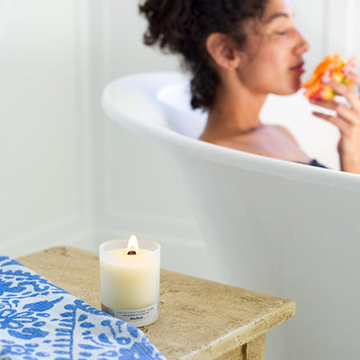 Woman in bathtub next to Lemongrass Ylang Ylang essential oil candle for anxiety by Edens Garden