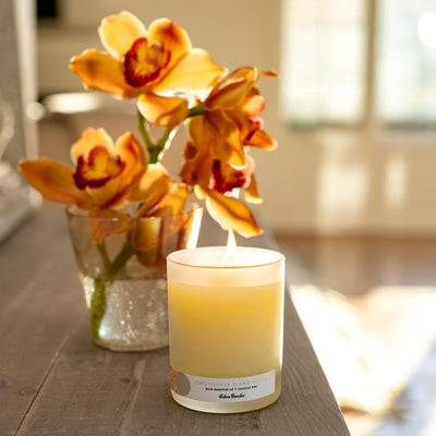 Orchids in vase next to Lemongrass Ylang Ylang essential oil candle for anxiety by Edens Garden