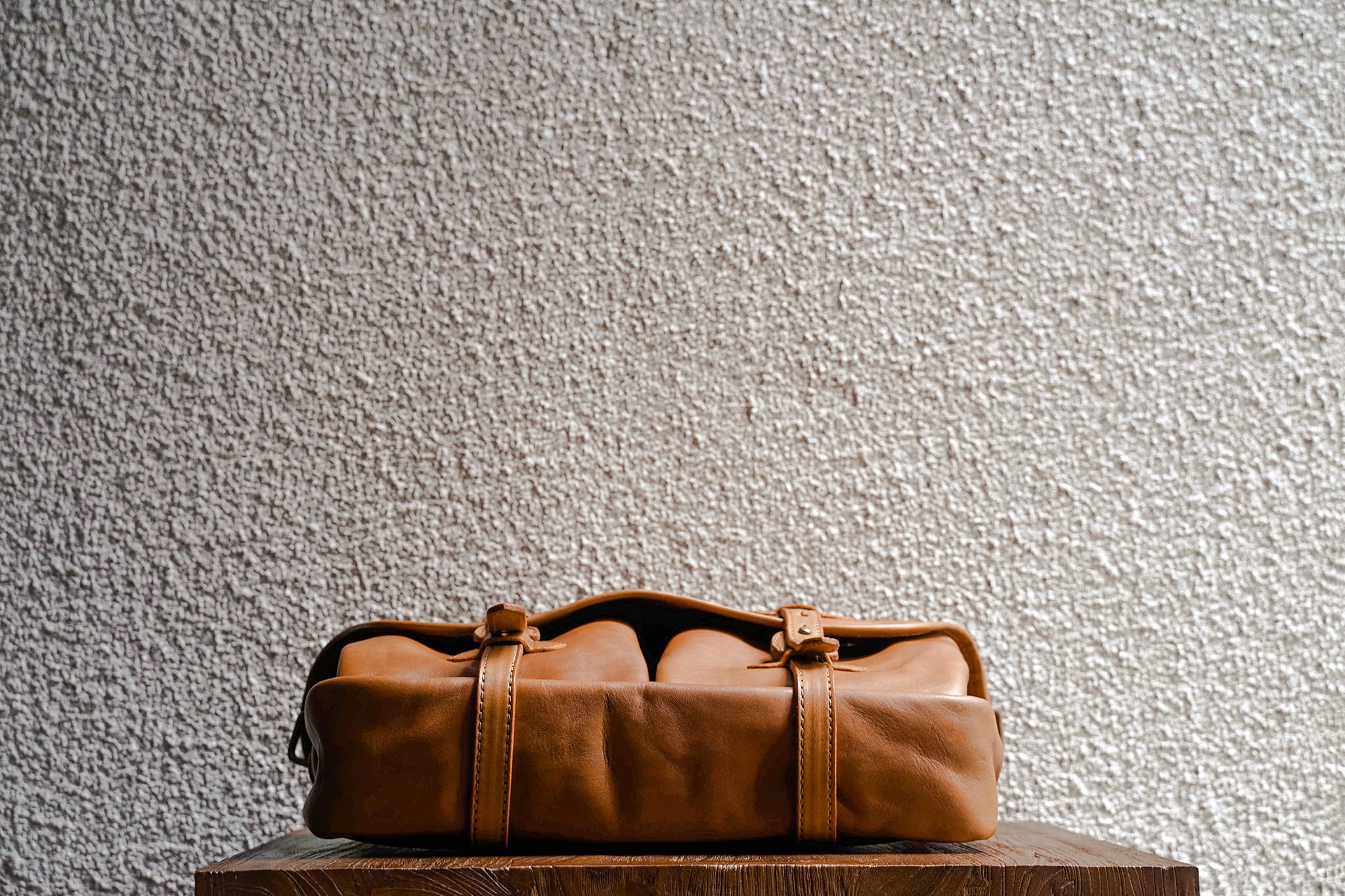 One of our signature design cues, the body straps go all around the bag, providing a load bearing structure for the bag. Keeping with the goal to minimize seams, the sides and bottom are made from one big piece of leather.