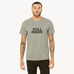 Still Inside screenprinted in black on heather stone unisex t-shirt.