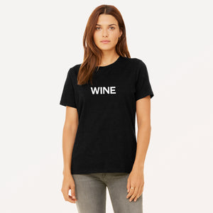 Wine screenprinted in white on heather black women's t-shirt.