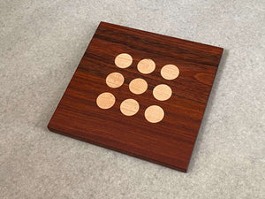 Square cutting and serving board in mahogany with 9 inlaid maple dots like tic tac toe.