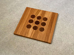 Square cutting and serving board in white oak with 9 inlaid walnut dots like tic tac toe.