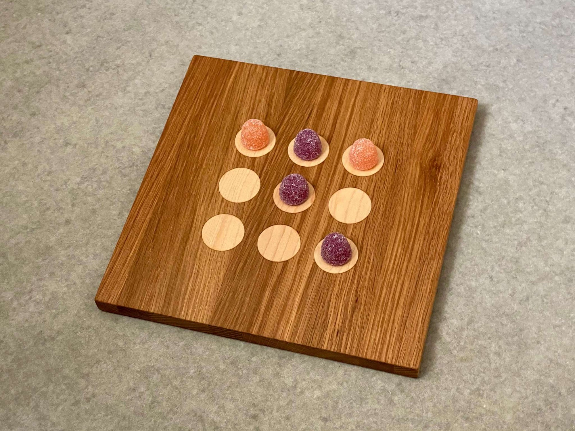 Square cutting and serving board in white oak with 9 inlaid maple dots like tic tac toe.