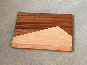 A rectangular board made of two shapes pieced together that resemble a maple mountain against a mahogany background. Sculpted edges provide natural fingerholds.