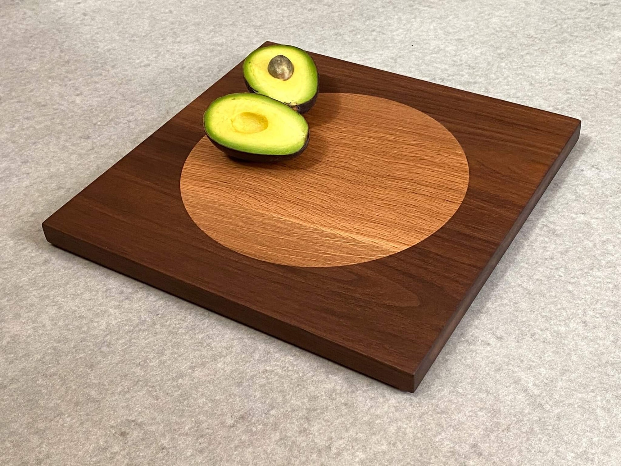 Square cutting board in walnut with large inlaid disc of white oak.