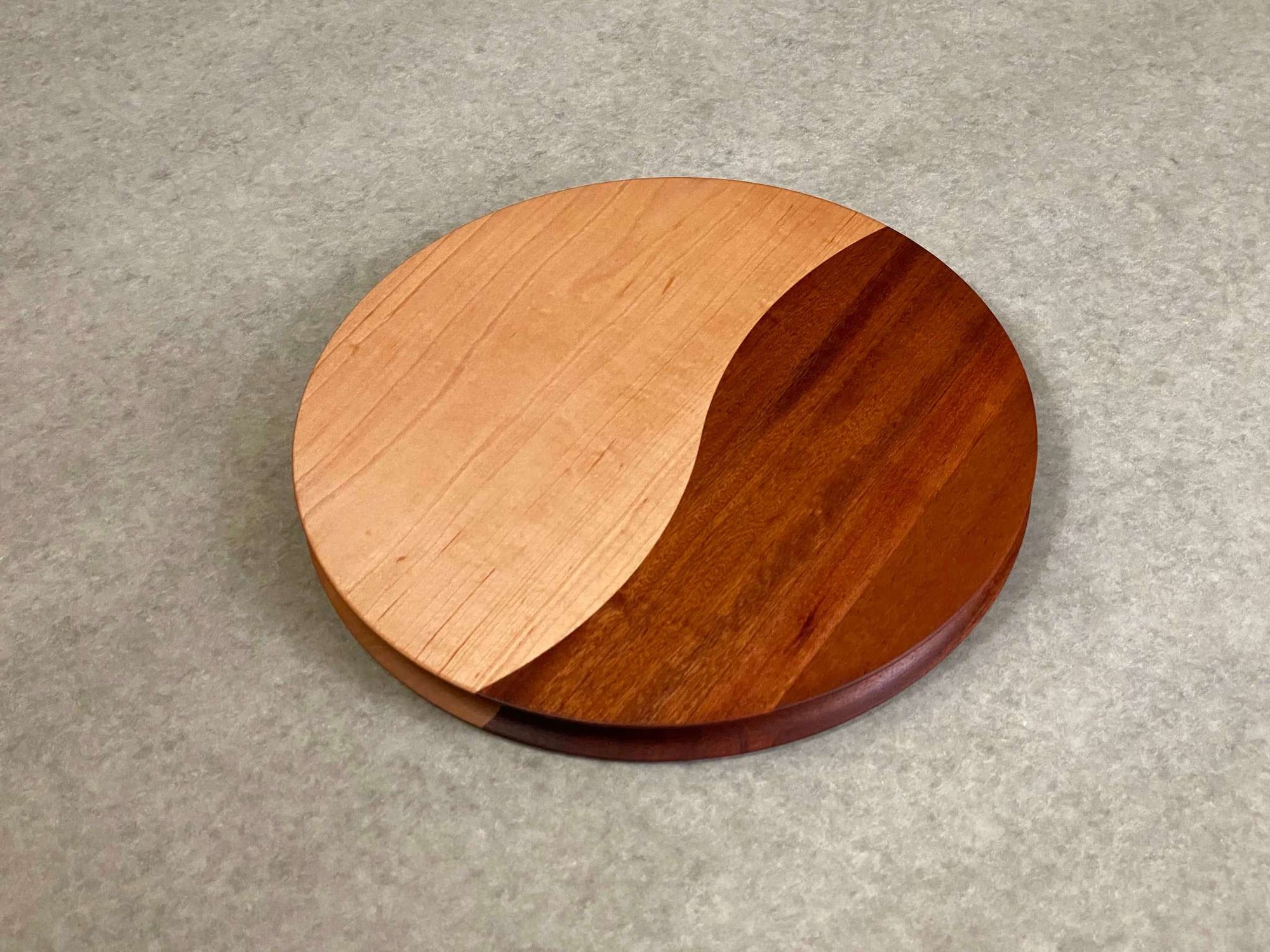 A round cutting and serving board made of part walnut and part mahogany with an off center curving joint. Sculpted edges provide a nice detail.