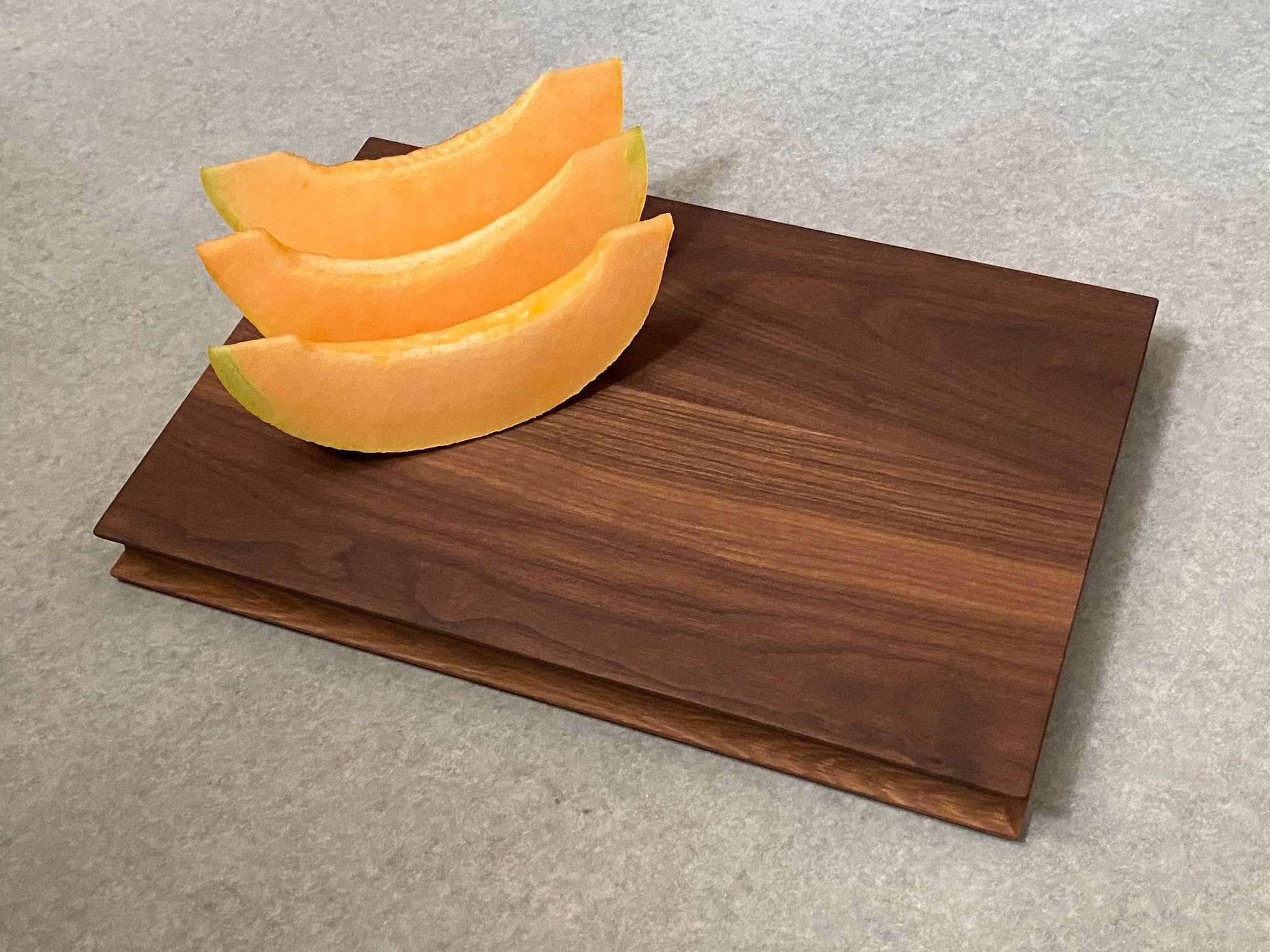Rectangular cutting and serving board that is white oak on one side and walnut on the reverse. Shaped edges provide comfortable fingerholds.