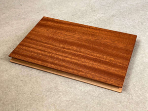 Rectangular cutting and serving board that is mahogany on one side and maple on the reverse. Shaped edges provide comfortable fingerholds.