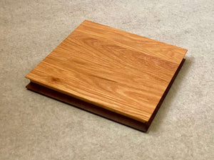 Square cutting and serving board made of white oak on one side and walnut on the reverse. Sculpted edges provide comfortable fingerholds.