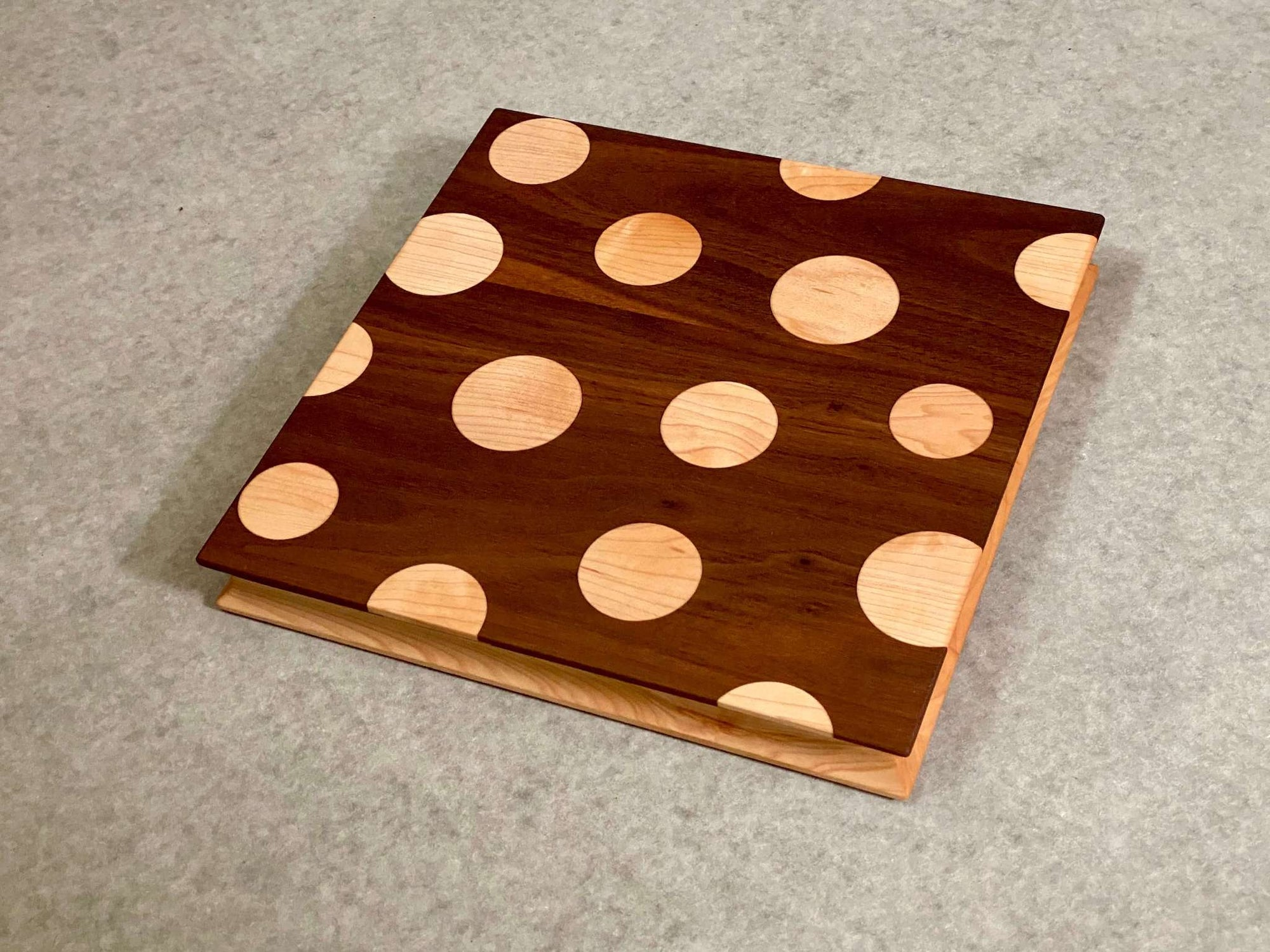 Square cutting and serving board made of walnut with inlaid maple polka dots on one side and solid maple on the reverse. Sculpted edges provide comfortable fingerholds.