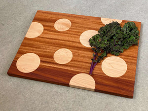 Large rectangular cutting and serving board of mahogany with large inlaid maple dots. Pattern is on both sides.