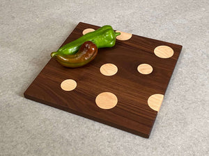 Square cutting and serving board in walnut with inlaid maple dots.