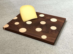 Small rectangular board of walnut with inlaid polka dots of maple. Pattern is on both sides.