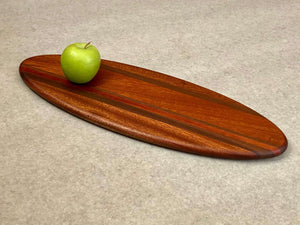 A large ellipse shaped cutting and serving board made of mahogany with thin stripes of walnut.