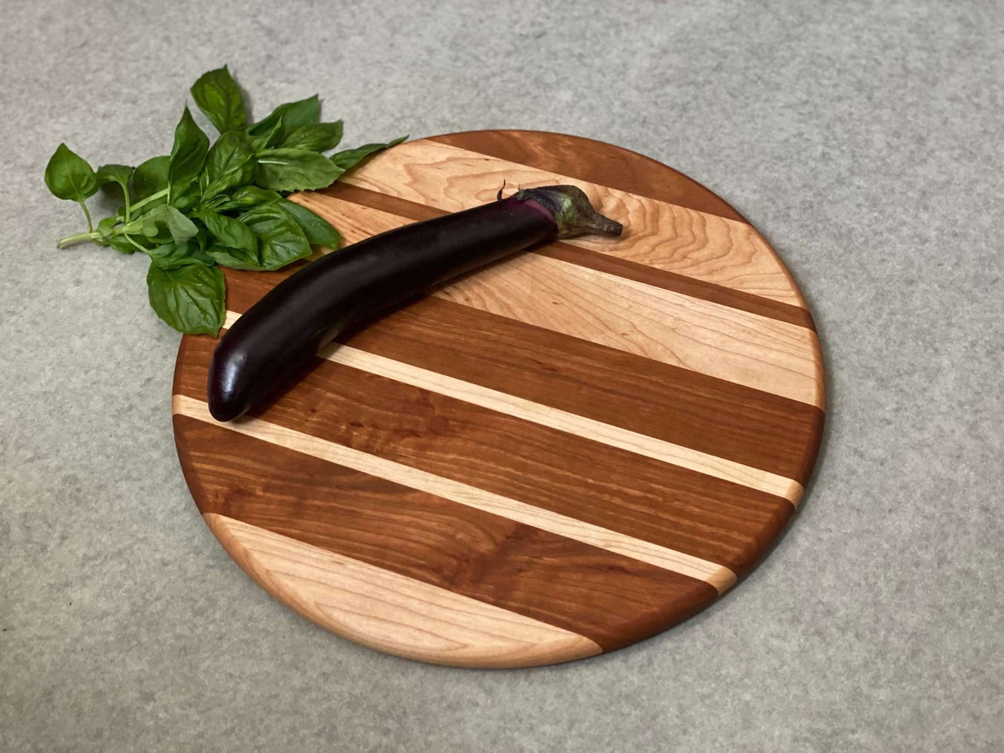 Round cutting and serving board of thick and thin stripes of cherry and maple.