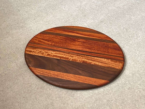 Oval shaped cutting and serving board in mahogany with walnut stripes.