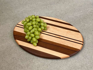 Oval shaped cutting and serving board in maple with walnut stripes.