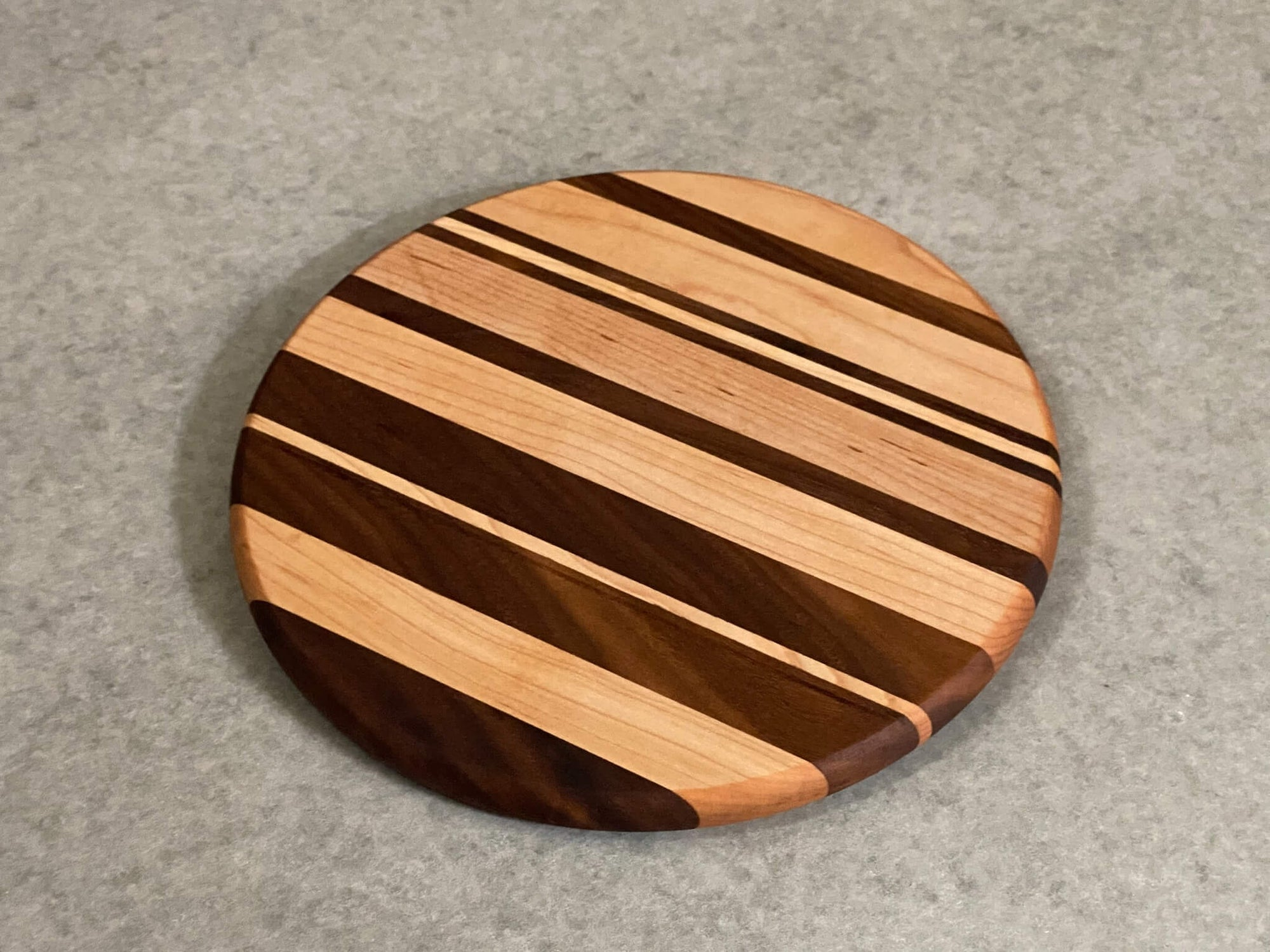 Small round cutting and serving board of maple and mahogany stripes.
