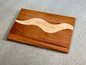 A rectangular cutting and serving board of mahogany with a bold squiggly stripe of maple. Sculpted edges provide comfortable fingerholds.