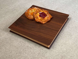 A square cutting and serving board of maple sandwiched between two thin layers of walnut. Sculpted edges provide comfortable fingerholds.