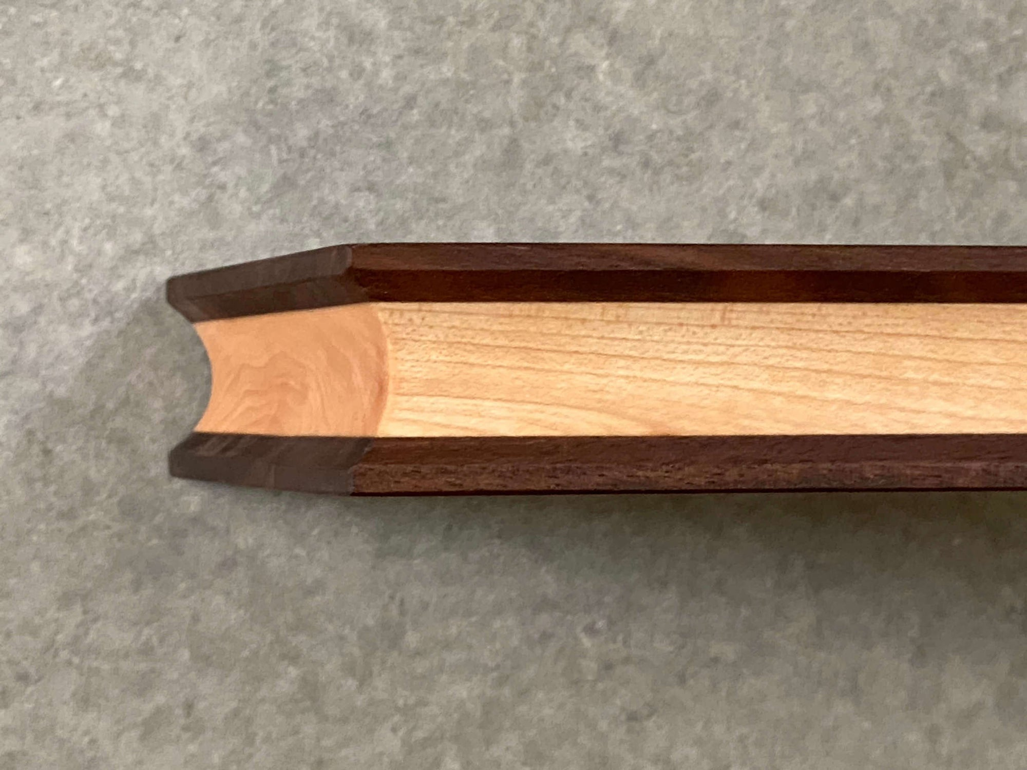 A long narrow rectangular cutting and serving board made of maple sandwiched between two thin layers of walnut. Sculpted edges provide comfortable fingerholds.