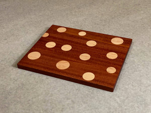 Small rectangular board of mahogany with inlaid polka dots of maple. Pattern is on both sides.