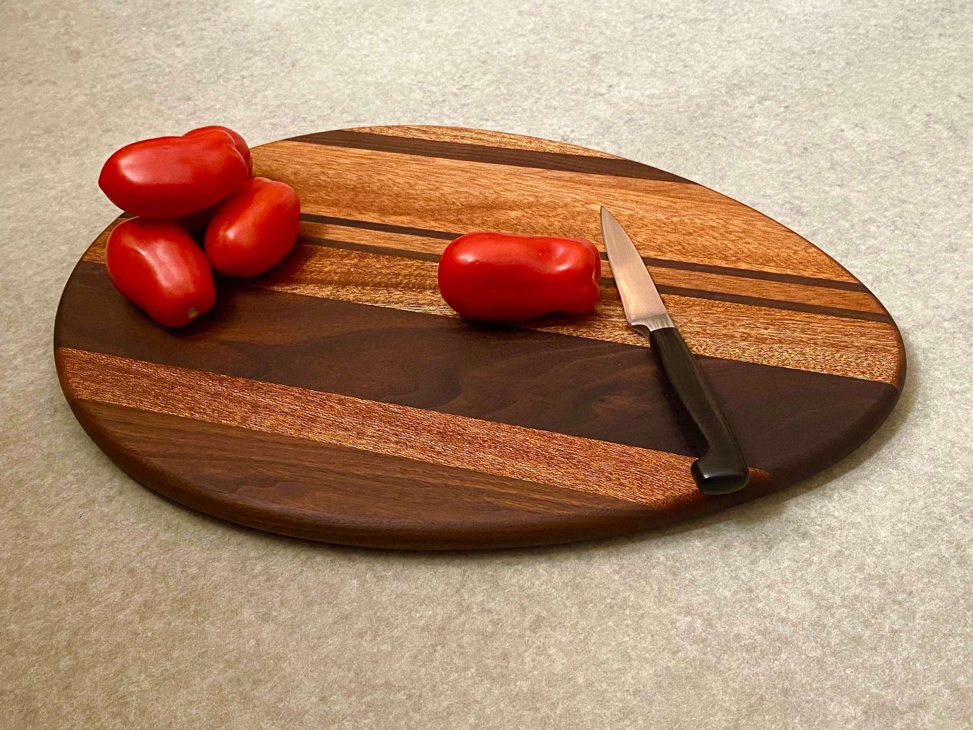 An egg shaped cutting and serving board with bold stripes of mahogany and walnut.