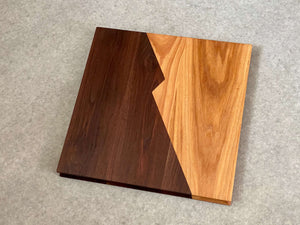 A square cutting and serving board that is half walnut and half hickory with a zigzag center joint. Sculpted edges provide comfortable fingerholds.