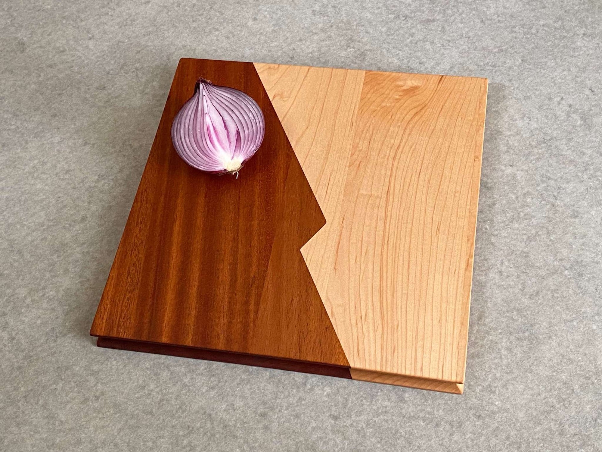 A square cutting and serving board that is half maple and half mahogany with a zigzag center joint. Sculpted edges provide comfortable fingerholds.