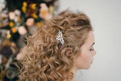 white woman with blonde natural curly hair styled with sparkly hair barrette for the holidays