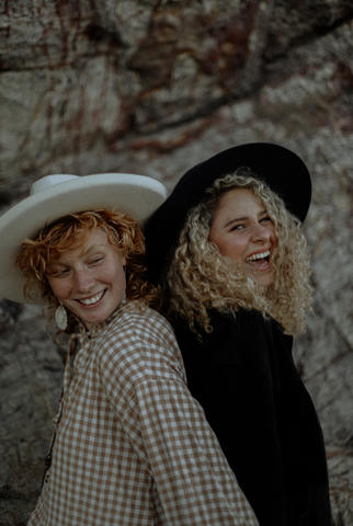 two girls with curly hair and hats