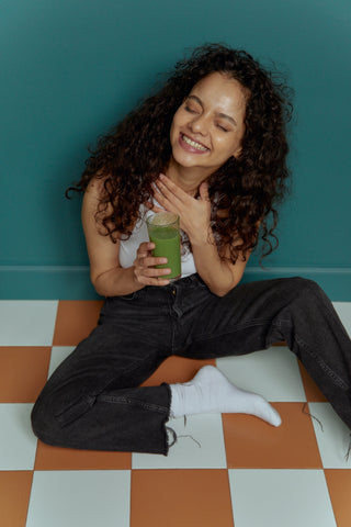 curly hair girl with green smoothie