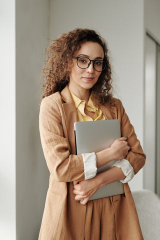 curly hair woman with glasses and laptop