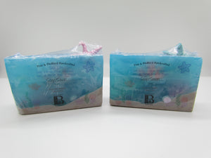 Pine and Bedford's Sea Life Soap. An almost transparent blue glycerin.  Each depicts a soapy underwater sea world.  You can see the sand at the bottom of the ocean, some coral growing on the side, a pearl from a hidden clam and a star fish floating on the surf at the top.  What you may not be able to see is a clown fish (like Nemo) a clam and some gold dust left behind by pirates.