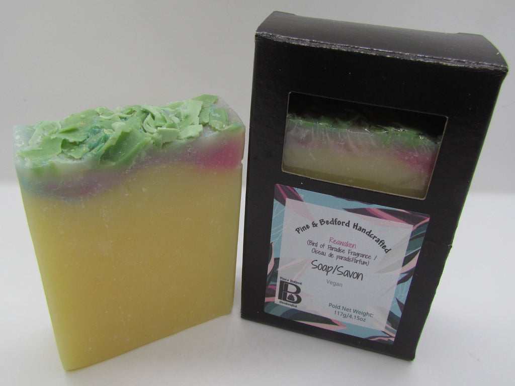Pine and Bedford's Reawaken (Bird of Paradise) Soap. A muted orangey-yellow colour, with pink and blue toward the top of the bar with green soap shavings on top. Shown here naked and also boxed.