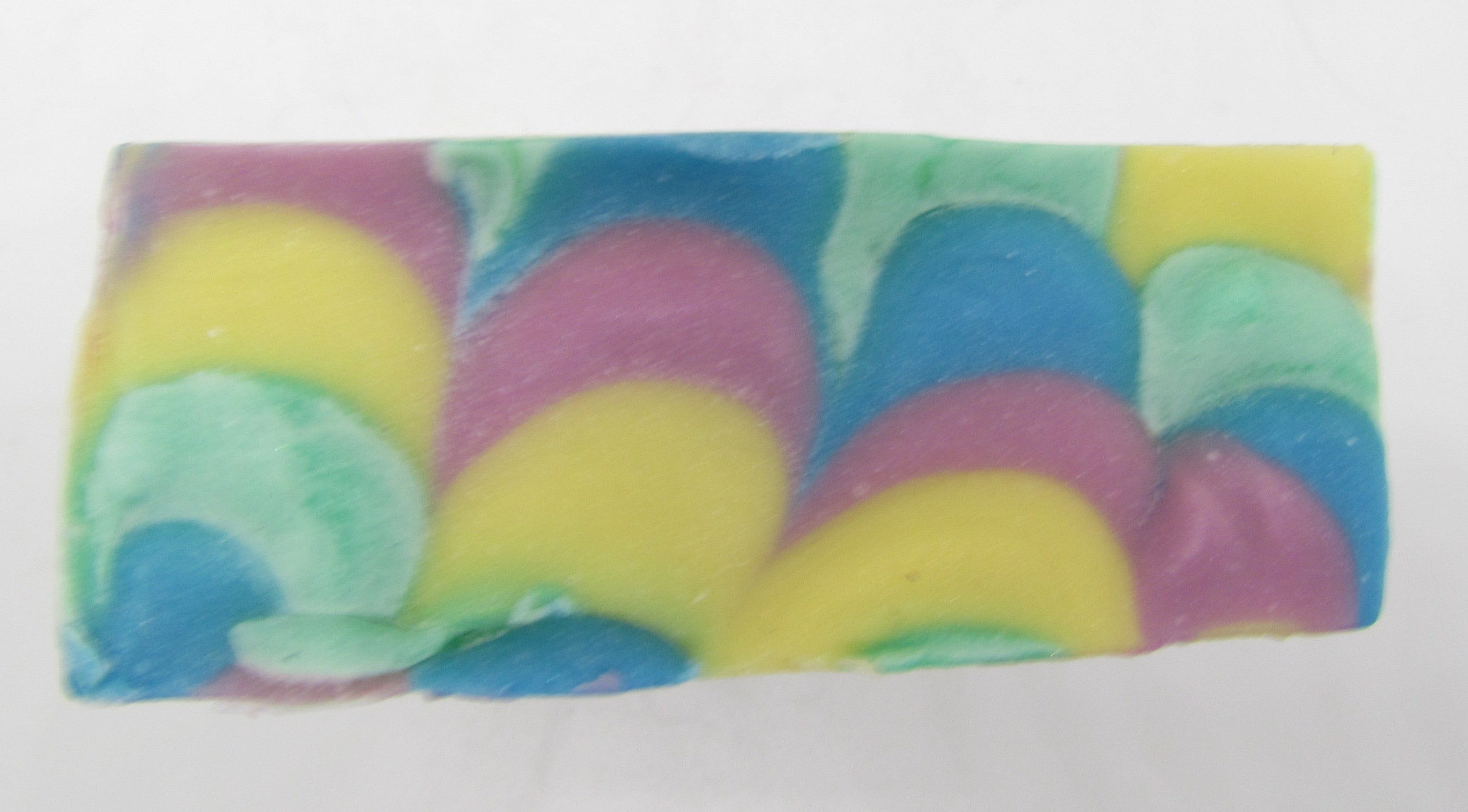 Pine and Bedford's Rainbow Columns Soap (top). As is above is below. The top of this soap is also a rainbow -- with layers of yellow, pink, blue, and green in a waved pattern almost like a feather.