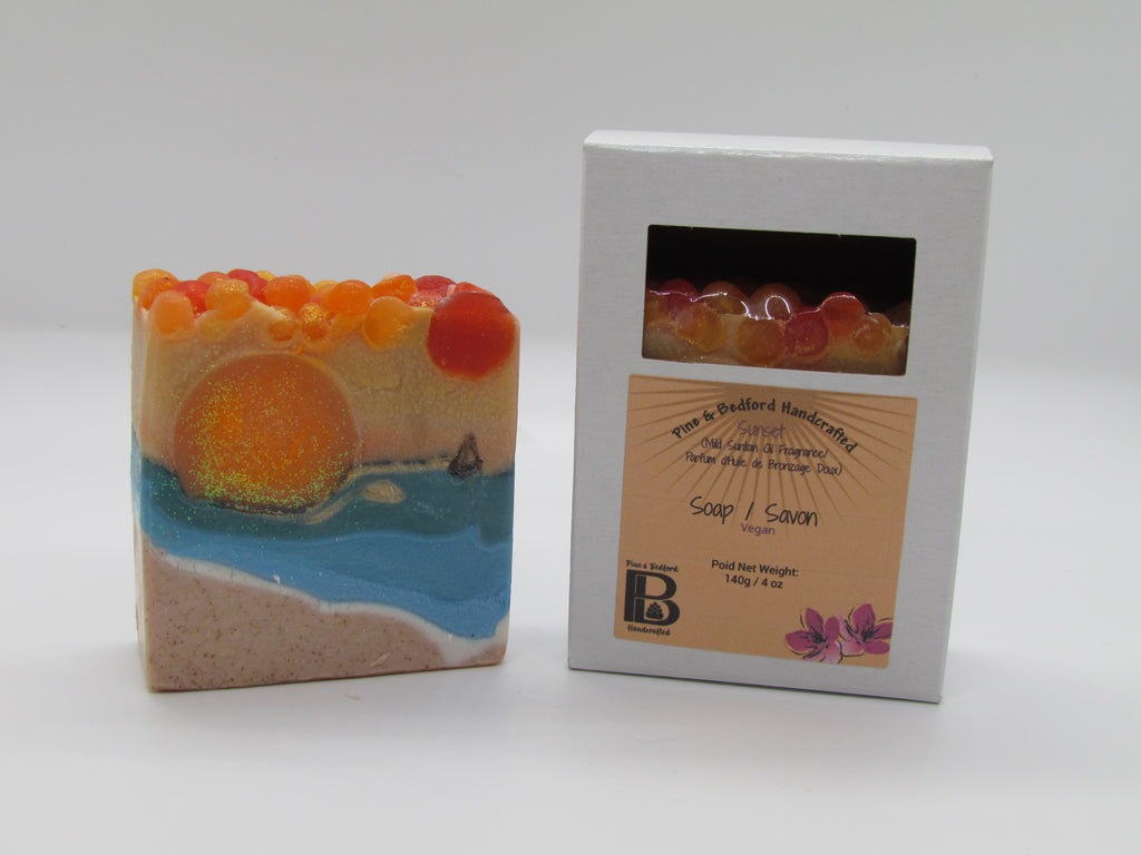 Pine and Bedford's Sunset landscape soap with a mild suntan lotion scent in orange, blue, beige and white. The white soap box had a cutout to reveal the soap inside.
