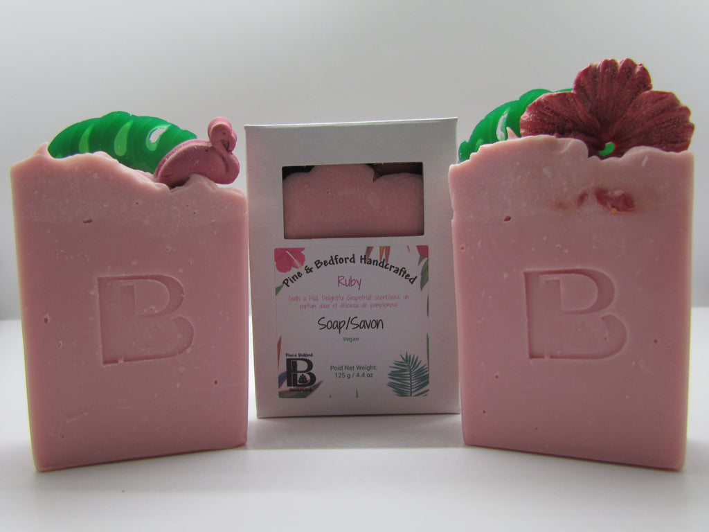 Pine & Bedford's Ruby soap is from our Luxurious Lather Collection. It is lightly fragrance with a fresh-grapefruit fragrance oil.  It is pink with top embellishments of green palm leaves and either a rosy hibiscus or pink flamingo.  Shown naked and boxed.