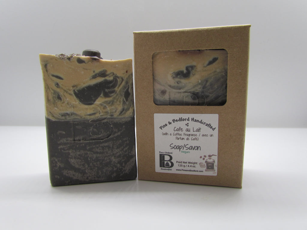Pine and Bedford's Cafe Au Lait bar soap. The top is embellished with soapy coffee beans and faux black & brown coloured sugar (The sugar is made from Dead Sea salts). Shown naked and boxed.