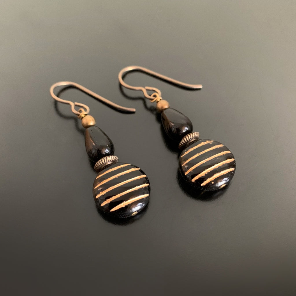 dangle earrings with a black and gold striped coin shaped bead