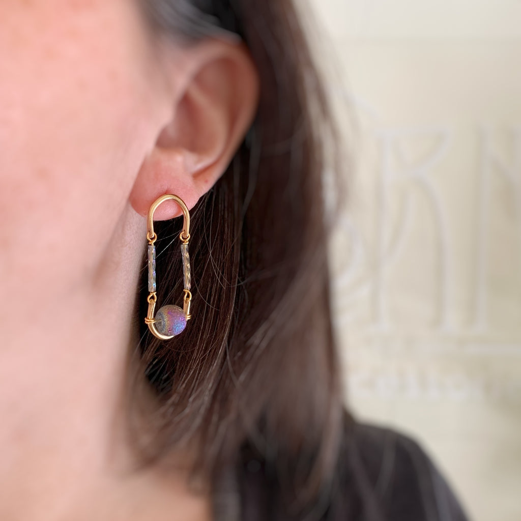 purple glass that has an ancient look, set in a golden brass drop and sterling silver post earring resembling architectural columns and arches