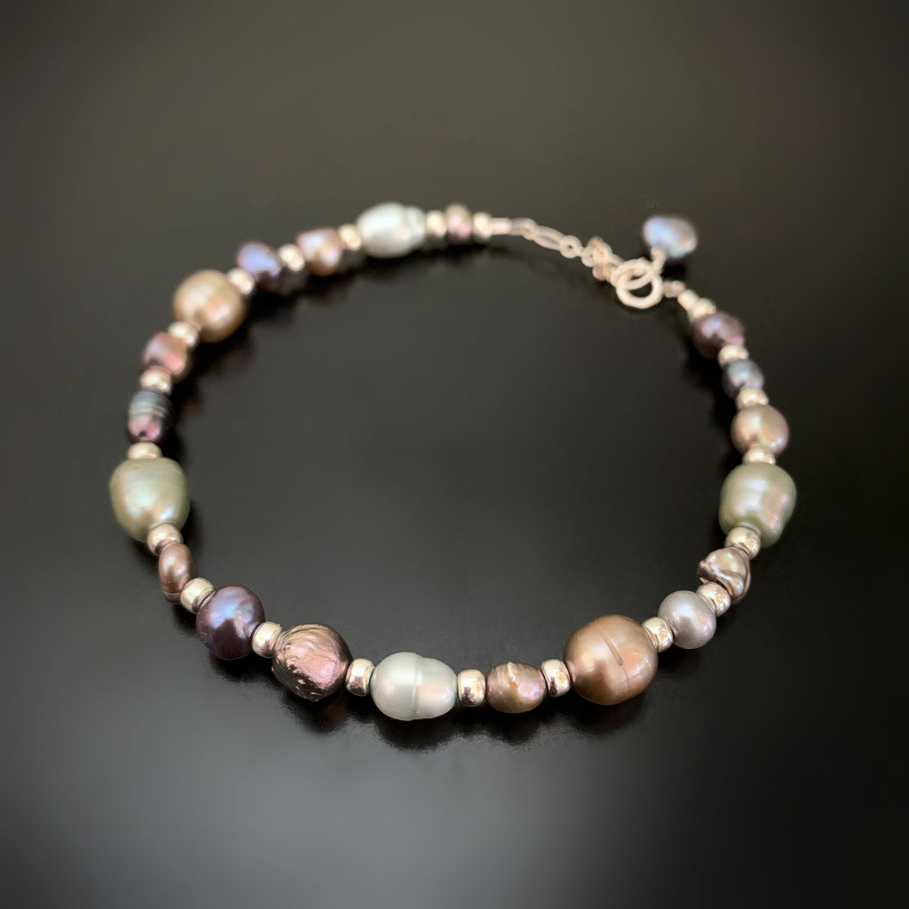 freshwater pearl bracelet with a mix of shapes, sizes and colors in the blue, green and purple tones