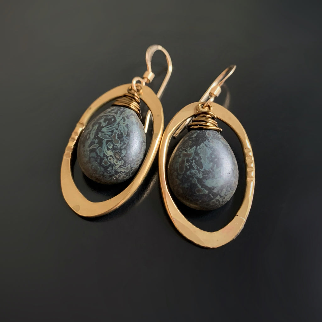 earrings with black and grey glass teardrops inside brass ovals