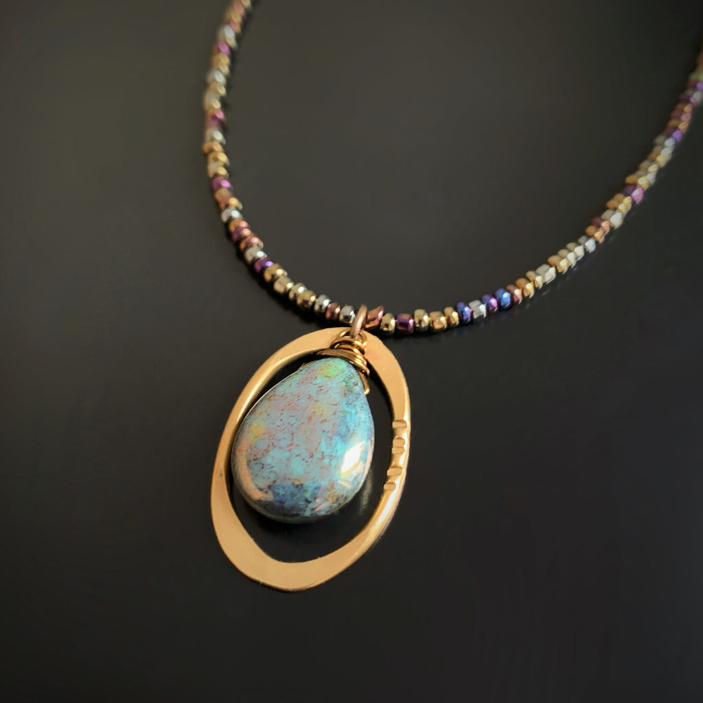 necklace with a blue and gold mottled glass teardrop inside a brass oval