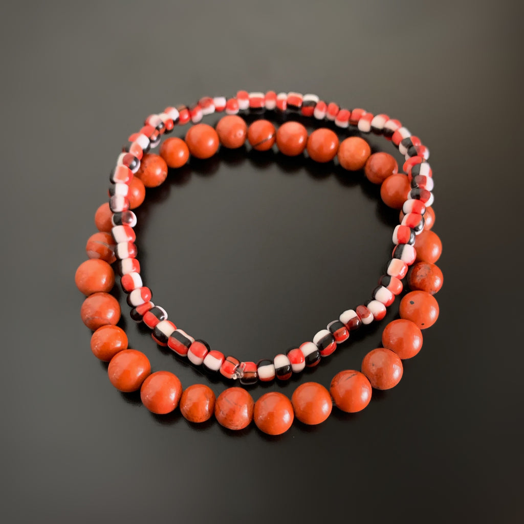 Pair of stretch bracelets, one in red jasper, and one in red, black and white striped glass