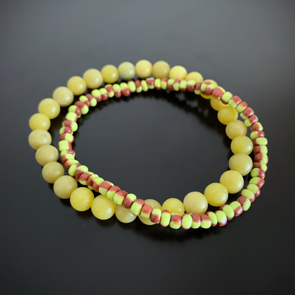 Pair of stretch bracelets, one in olivine green jade, and one in green and brown striped glass