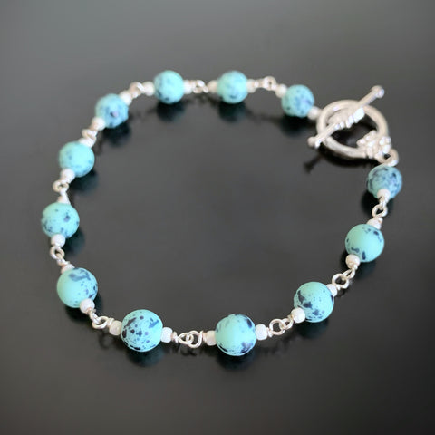 turquoise speckled glass beads linked together to create the bracelet